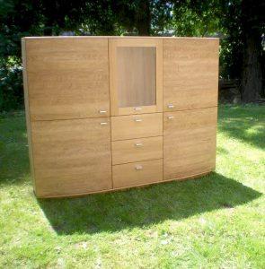 <ul>   <li> Wohnschrank in Eiche massiv, Türen nach Außen, ca. 5 cm gerundet, 3 massive Schubladen und 4 Holztüren und 1 Glastür</li>    <li>Oberfläche: Eiche matt geölt</li>    <li>Maße: ca. 180 x 130 x Mitte 48 Außen 43 (B x H x T)</li>    <li>Holzart: Eiche massiv</li></ul>